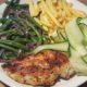 Kip met Caribische touch, haricots verts, fris-zure komkommer en ovenfriet